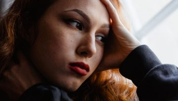 woman looks out the window and contemplates going to rehab even though she is feeling scared