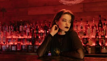 woman sitting at a bar feeling suicidal after binge drinking